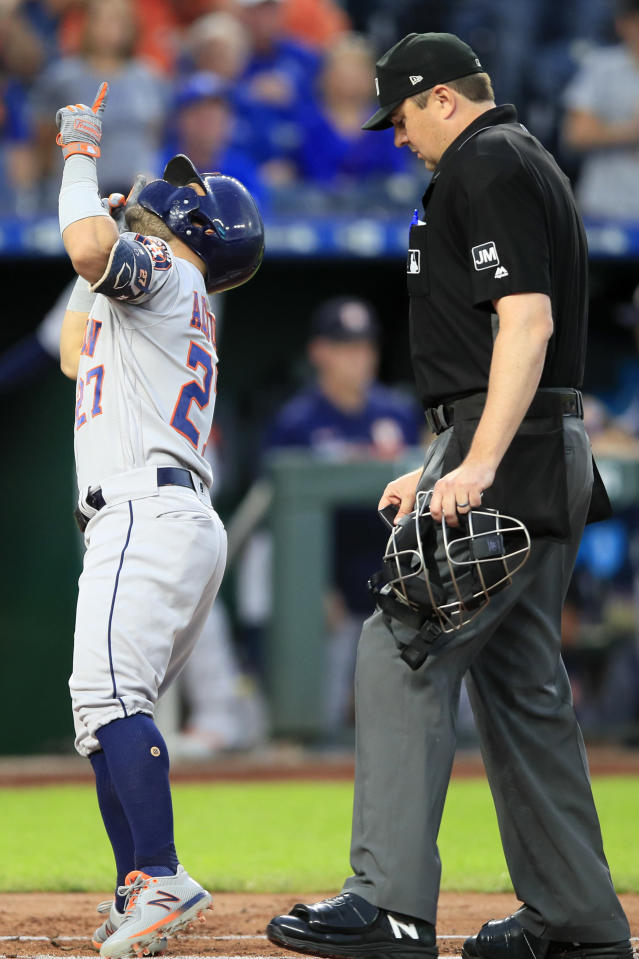Houston Astros' Jose Altuve gestures next to home plate umpire Lance Barrett following his solo home run during the first inning of the team's baseball game against the Kansas City Royals at Kauffman Stadium in Kansas City, Mo., Friday, Sept. 13, 2019. (AP Photo/Orlin Wagner)