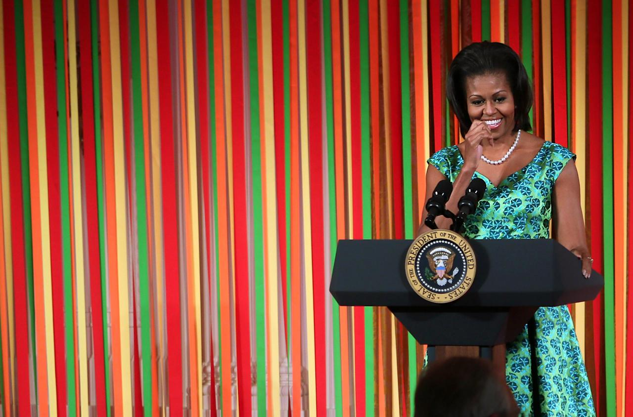 """WASHINGTON, DC - AUGUST 20:  U.S. first lady Michelle Obama speaks during a Kids' """"State Dinner"""" luncheon at the East Room of the White House August 20, 2012 in Washington, DC. Fifty-four kids representing all U.S. states, three territories and the District of Columbia, ages 8-12 and winners of the Healthy Lunchtime Challenge to create a healthy, affordable and tasty lunchtime recipe with nutritional guidelines set by the Agriculture Department, were invited to participate in the event.  (Photo by Alex Wong/Getty Images)"""