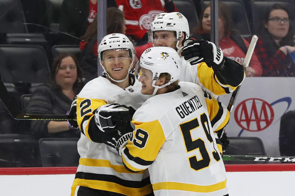 Pittsburgh Penguins defenseman Chad Ruhwedel (2) celebrates his goal with Marcus Pettersson (28) and Jake Guentzel (59) in the first period of an NHL hockey game against the Detroit Red Wings, Saturday, Dec. 7, 2019, in Detroit. (AP Photo/Paul Sancya)