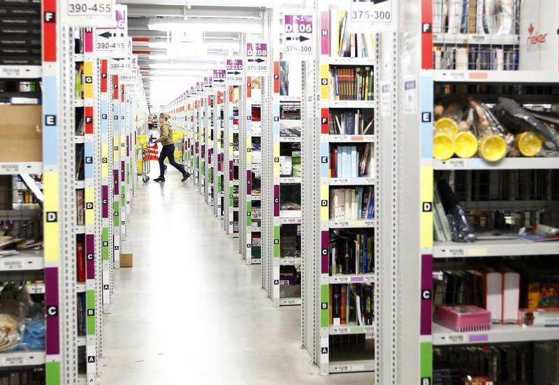 Worker collects items to pack into boxes at Amazon's logistics centre in Graben