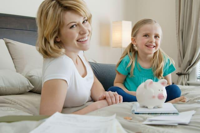 BM7Y94 Mother and daughter saving money  Motherdaughtersavingmoney; Saving; money18-19; years20-25; years5-6; yearsChild
