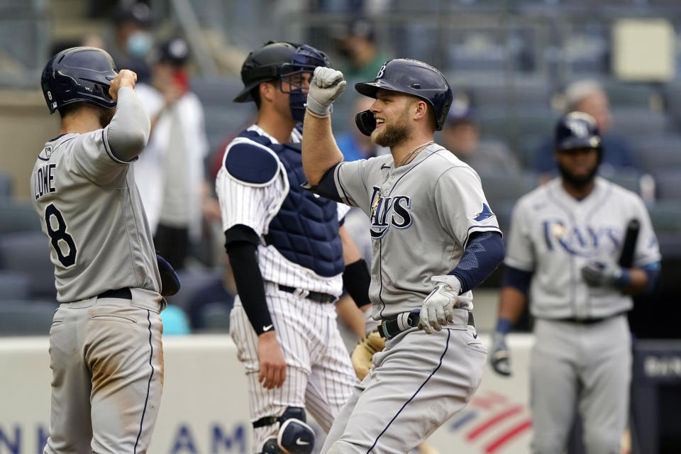 Tampa Bay Rays designated hitter Austin Meadows, center, is greeted by Brandon Lowe (8) after hitting a two-run home run during the fourth inning of a baseball game against the New York Yankees, Thursday, June 3, 2021. (AP Photo/Kathy Willens)