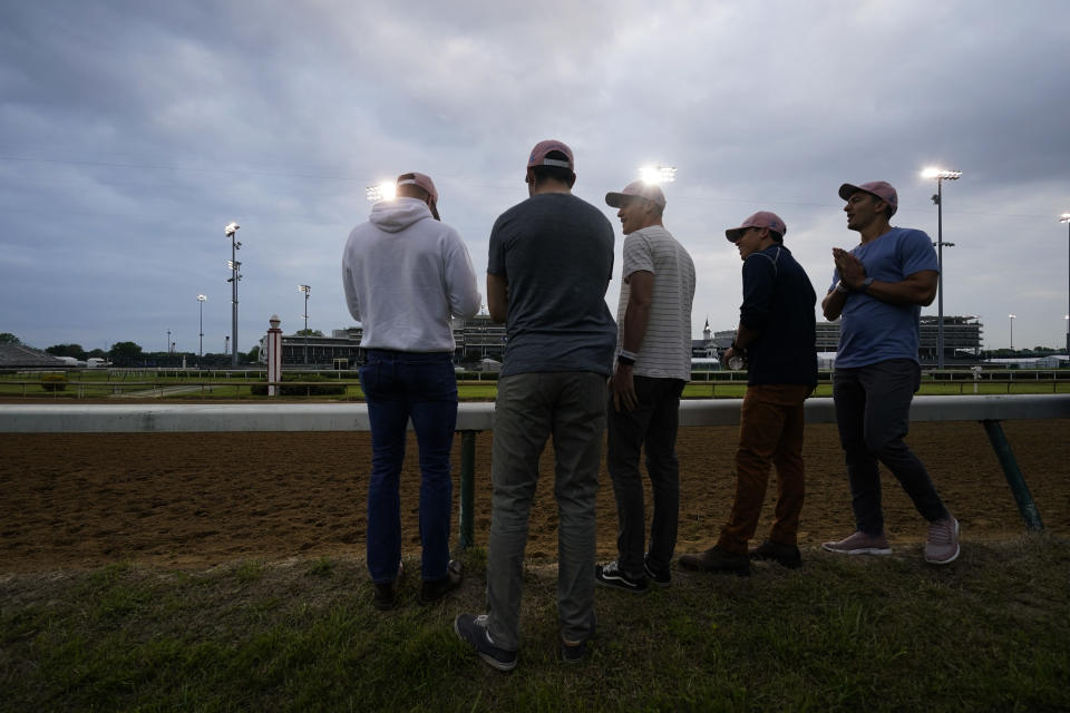 Former college teammates from left to right, Eric Armagost, Alex Quoyeser, Reiley Higgins, Patrick O'Neill and Dan Giovacchini, wait to watch Kentucky Derby entrant Hot Rod Charlie workout at Churchill Downs Wednesday, April 28, 2021, in Louisville, Ky. The group own 25% of the horse being trained by O'Neill's uncle Doug O'Neill. (AP Photo/Charlie Riedel)