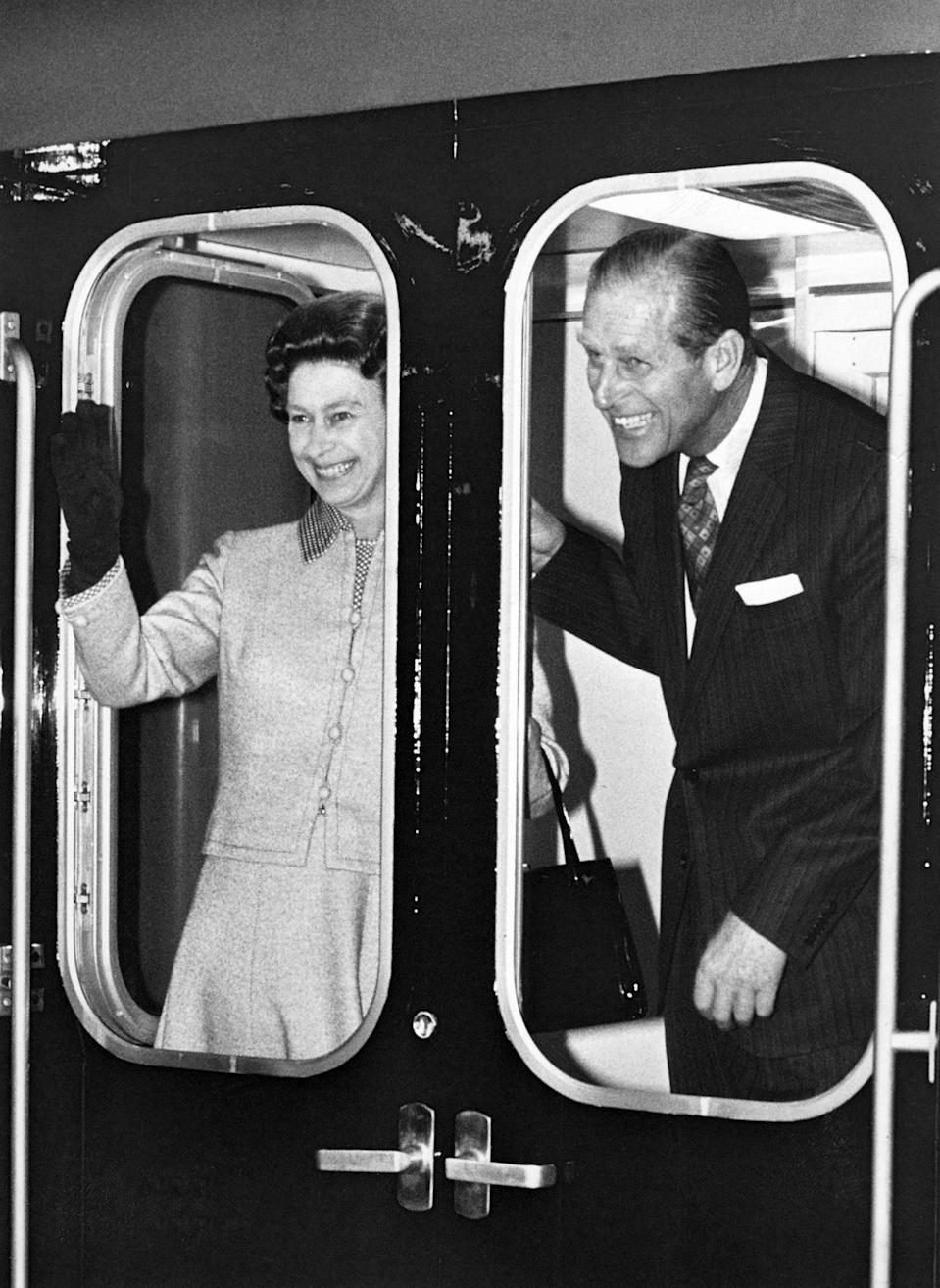 <p>The Prince and his wife - who he affectionately called 'cabbage' - made time for fun while on official royal duty. Here the pair grin and wave madly from a train in May 1977. Photo: Getty Images.</p>