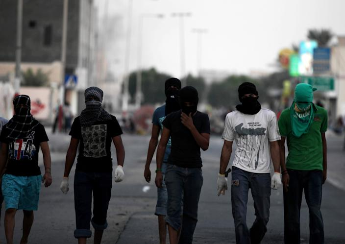 """Masked Bahraini anti-government protesters walk away from a barricade as blocking a street in the western village of Malkiya, Bahrain, Tuesday, Aug. 13, 2013. Inspired by the movement behind Egypt's military coup, pro-democracy activists in Bahrain are hoping to gain new momentum by calling for nationwide protests Wednesday. Authorities warned they will """"forcefully confront"""" any large demonstrations, raising fears of more violence in the strategic Gulf kingdom. (AP Photo/Hasan Jamali)"""