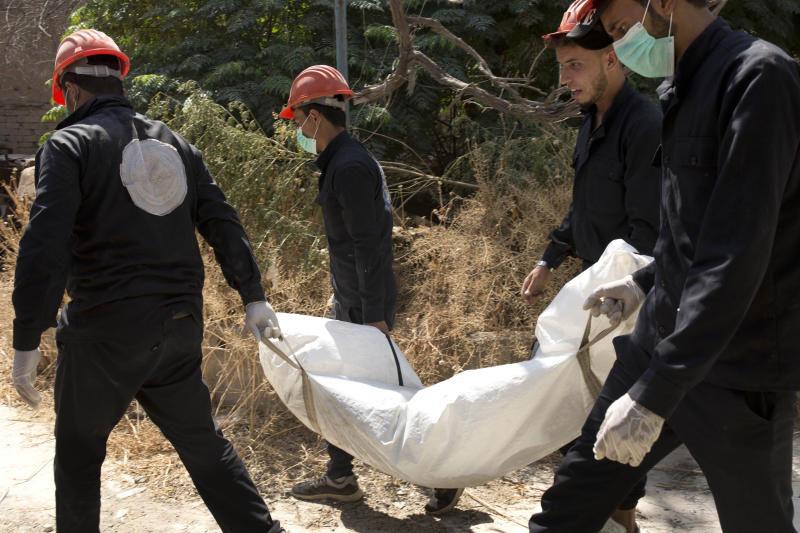 In this Saturday, Sept. 7, 2019, photo, first responders remove a body at the site of a mass grave in Raqqa, Syria. First responders say they have pulled nearly 20 bodies out of the latest mass grave uncovered in Raqqa, the Syrian city that was the de facto capital of the Islamic State group. It is the 16th mass grave in the city, and officials are struggling with a lack of resources needed to document and one day identify the thousands of dead who have been dug out. (AP Photo/Maya Alleruzzo)