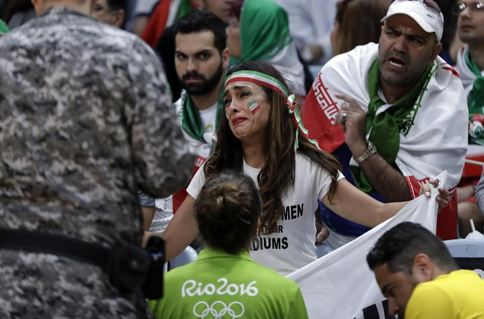 A woman is confronted by Olympic officials for holding a sign that reads,