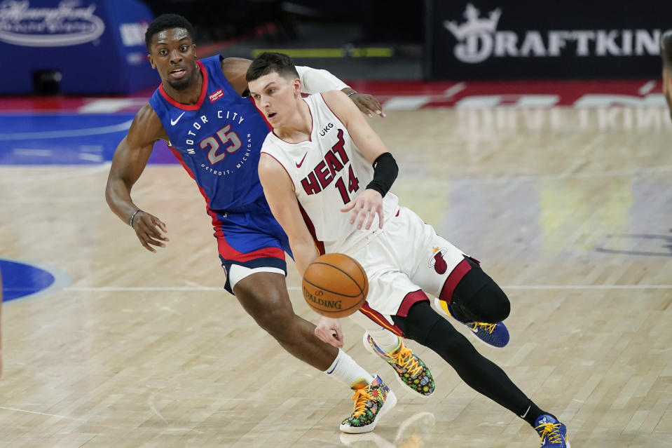 Miami Heat guard Tyler Herro (14) brings the ball up court as Detroit Pistons forward Tyler Cook (25) defends during the first half of an NBA basketball game, Sunday, May 16, 2021, in Detroit. (AP Photo/Carlos Osorio)