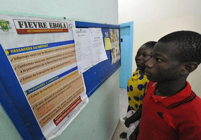 People read a poster bearing informations for travellers arriving in or departing from areas affected by the Ebola virus, on August 8, 2014 at the national public health institute in Abidjan