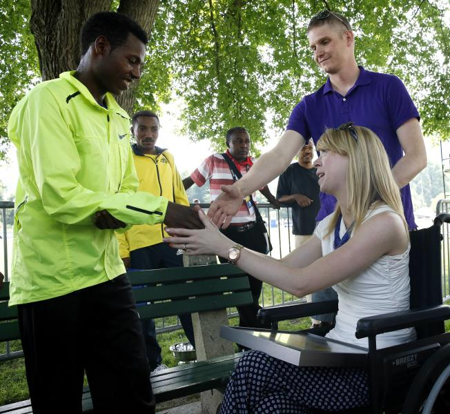 Boston Marathon 2013 men's winner Lelisa Desisa, left, of Ethiopia, greets Boston Marathon bombing victims Adam Davis, top right, and his wife Adrianne Haslet-Davis, Sunday, June 23, 2013, in Boston. Lelisa ran in the Boston Athletic Association 10k after which he presented his 2013 winners medal as a gift to the city in tribute to the victims of the bombing at the Boston Marathon finish line in April. (AP Photo/Michael Dwyer)