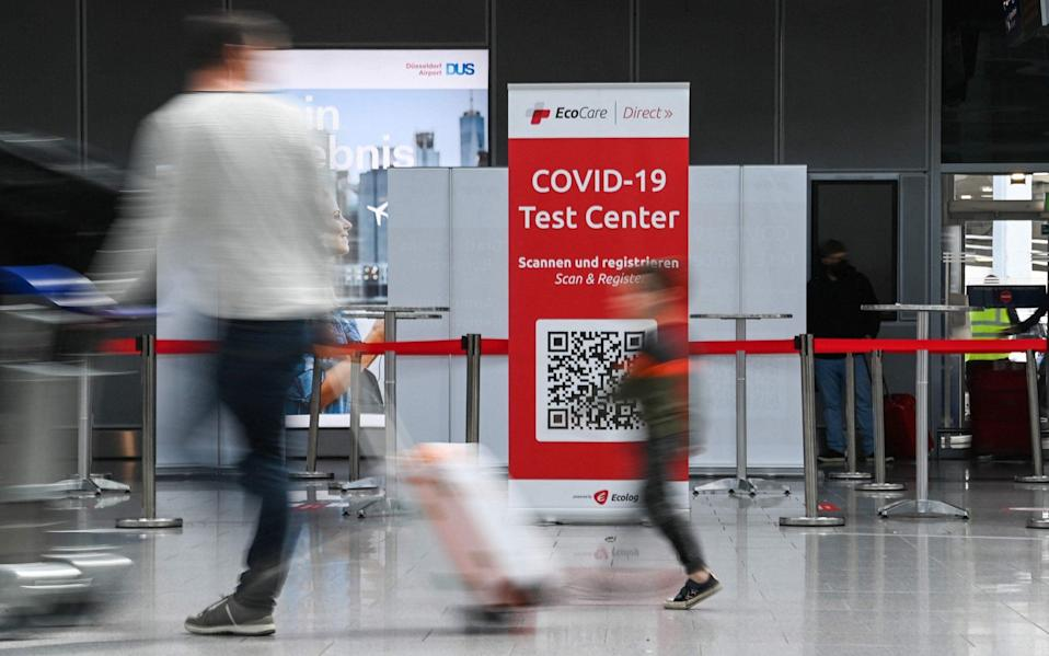 Travellers walk past a coronavirus COVID-19 rapid test center on July 2, 2021 at the airport of Duesseldorf - INA FASSBENDER/AFO