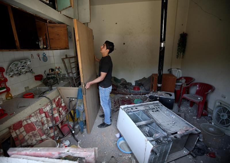 A Lebanese man removes a broken door inside his damaged home, due to rockets fired by Syrian rebels according to the villagers, in Hermel town, northeast of Lebanon, Wednesday May 29, 2013. Shells fire from Syria regularly strike the Lebanese northeastern town of Hermel, a predominantly Shiite town. Sectarian tensions in Lebanon have been on the rise, particularly as a result of the involvement of the militant Hezbollah group in fighting in Syria alongside President Bashar Assad's forces. (AP Photo/Hussein Malla)