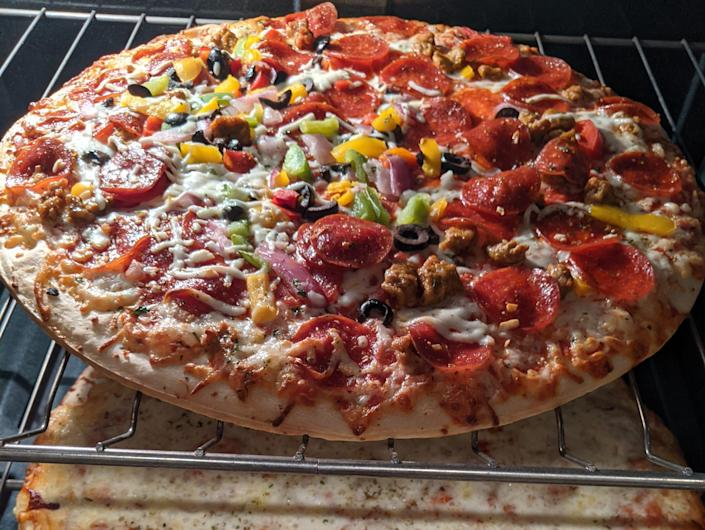 Two pizzas - one loaded with veggies and one with cheese - sitting on oven racks