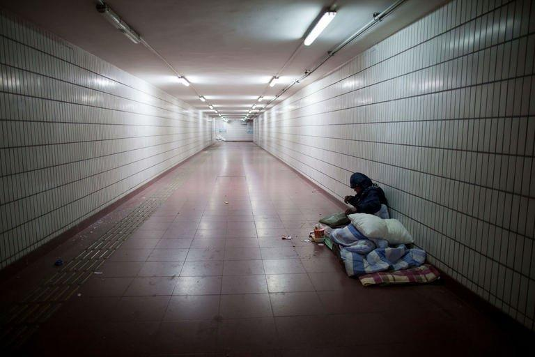 A homeless man lies on his bed in an underpass in Beijing on December 7, 2012