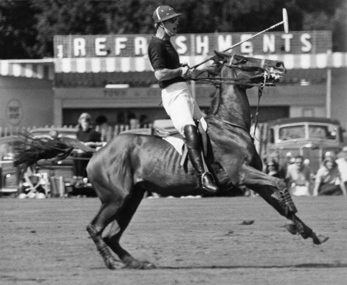 FILE - In this June 20, 1965 file photo, Britain's Prince Philip pulls his mount up sharp during a polo match at Windsor, England. His team won the match. Buckingham Palace says Prince Philip, husband of Queen Elizabeth II, has died aged 99. (AP Photo/File)
