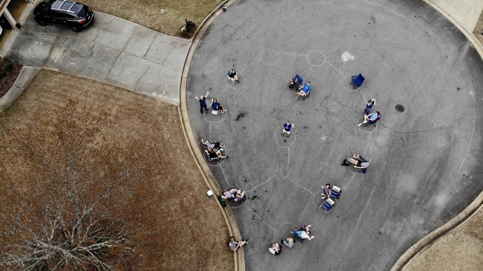 Neighbors in a metro Atlanta neighborhood gathered for a spontaneous block party, after drawing social distancing pods, spaced six feet apart, on the street with chalk. (Photo: Walt Deetz)