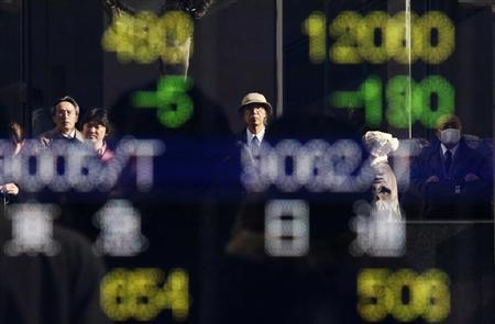 Pedestrians are reflected in an electronic board showing stock prices outside a brokerage in Tokyo December 12, 2013. REUTERS/Yuya Shino