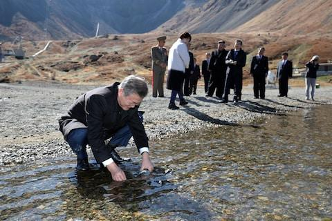 South Korean President Moon Jae-in collects water from heaven lake at the bottom of Mount Paektu during a visit with his North Korean counterpart Kim Jong-un on September 20, 2018 in Mount Paektu, North Korea - Credit: Getty Images AsiaPac