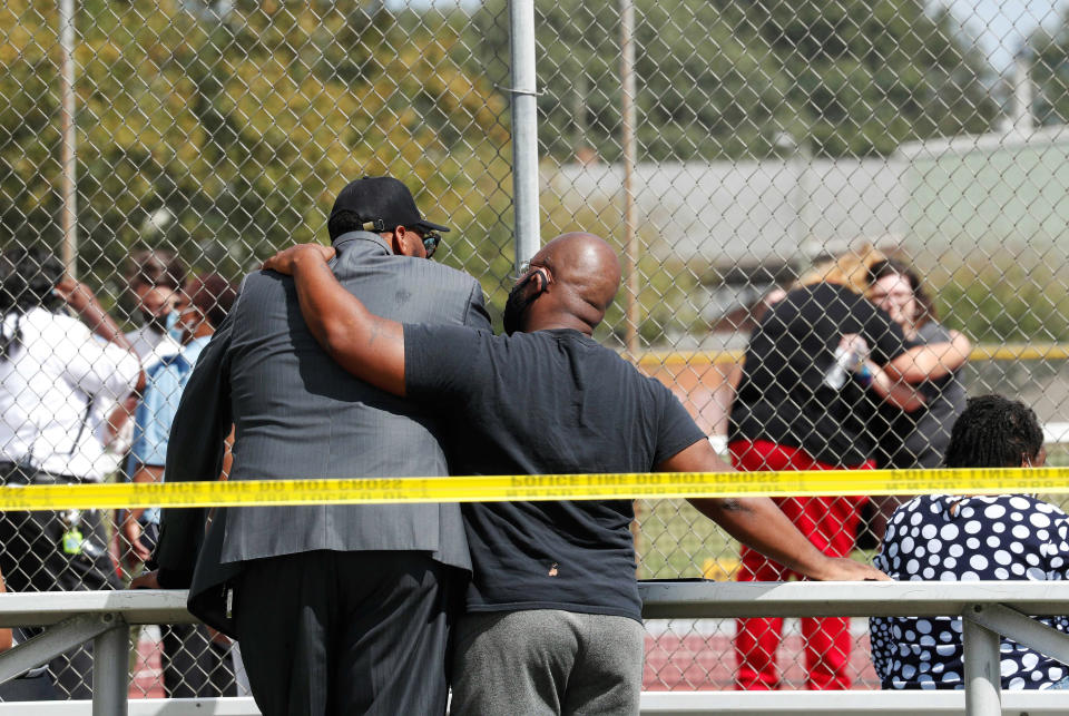 People console one another outside Heritage High School, near the tennis courts, following a shooting at the school, Monday, Sept. 20, 2021, in Newport News, Va. Students were evacuated to the tennis courts and parents were allowed to reunite with them there. (Jonathon Gruenke/The Virginian-Pilot via AP)