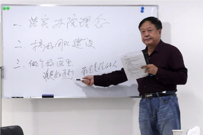 """In this Oct. 5, 2020, photo provided by the Legal Team of Dawu Group, Sun Dawu stands at a whiteboard at a hospital in Baoding in northern China's Hebei Province. A prominent Chinese pig farmer who was detained after praising lawyers during a crackdown on legal activists by President Xi Jinping's government has been sentenced to 18 years in prison on charges of organizing an attack on officials and other offenses. The board reads """"implement the concept of running the hospital, do a good job in team building, be a good doctor who is a good doctor, a responsible person."""" (Legal Team of Dawu Group via AP)"""