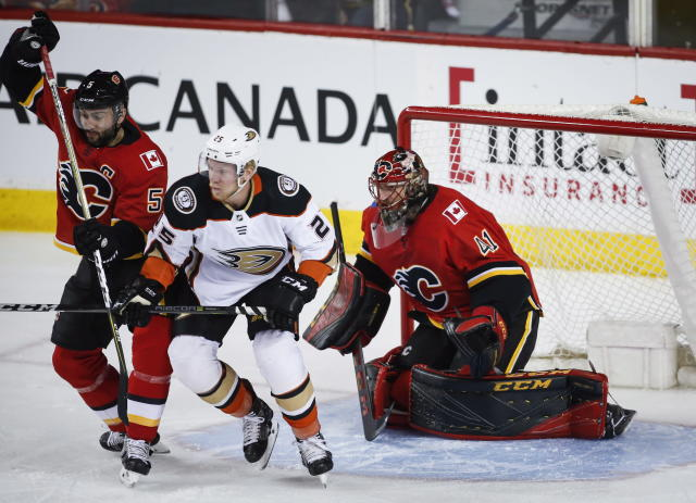 Anaheim Ducks right wing Ondrej Kase (25) fights for position with Calgary Flames defenseman Mark Giordano (5) in front of goaltender Mike Smith (41) during the first period of an NHL hockey game Wednesday, March 21, 2018, in Calgary, Alberta. (Jeff McIntosh/The Canadian Press via AP)