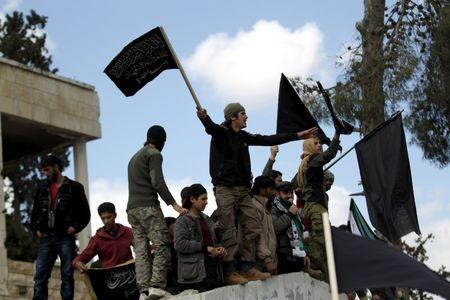Protesters carry Nusra Front flags and shout slogans during an anti-government protest after Friday prayers in the town of Marat Numan in Idlib province