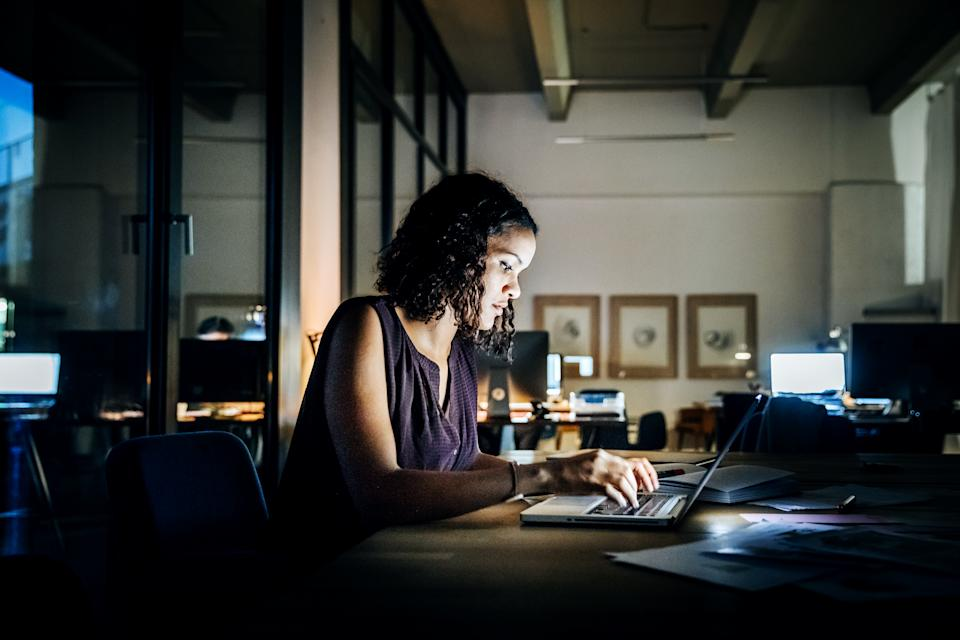 Casual young businesswoman working late on a laptop computer in a modern office space