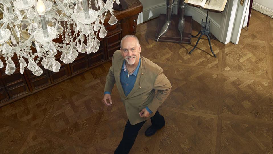 Garriott at home in New York. Behind him are a 17th-century Germanic suit of armor and other pieces from his collection of ancient artifacts. - Credit: Chris Buck