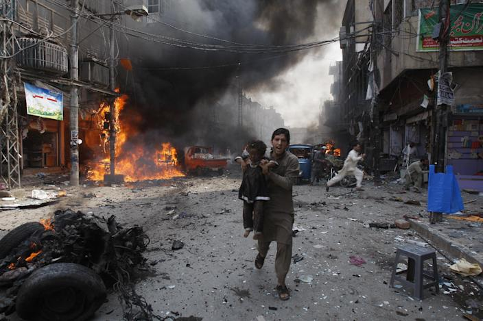 A Pakistani man carrying a child rushes away from the site of a blast shortly after a car exploded in Peshawar, Pakistan, Sunday, Sept. 29, 2013. A car bomb exploded on a crowded street in northwestern Pakistan Sunday, killing scores of people in the third blast to hit the troubled city of Peshawar in a week, officials said. (AP Photo/Mohammad Sajjad)