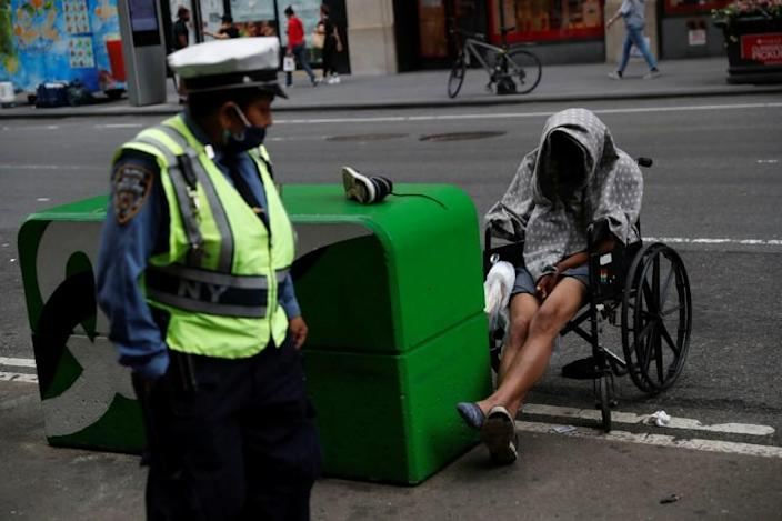A man sits in a wheelchair as a NYPD traffic officer passes by near Times Square in New York City