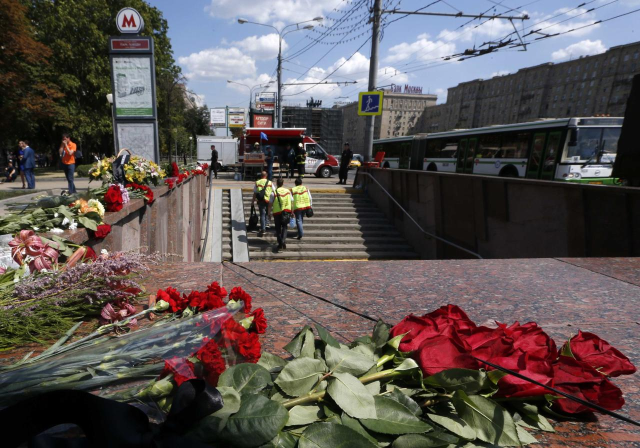Flowers are left in memory of victims of Tuesday's accident, in which three carriages derailed on a train during morning rush hour, at the entrance to a metro station in Moscow July 16, 2014. Russian state investigators said on Wednesday they had detained two Moscow metro workers suspected of safety breaches that may have caused an accident that killed at least 21 people. REUTERS/Sergei Karpukhin (RUSSIA - Tags: TRANSPORT DISASTER)
