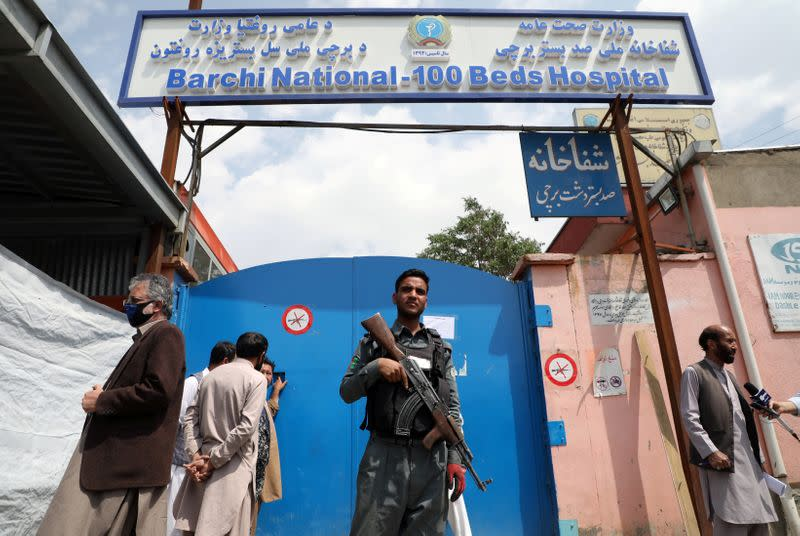 FILE PHOTO: An Afghan policeman keeps watch outside of a hospital which came under attack in Kabul