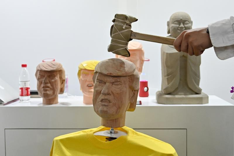 The Trump bobble-head kiosk was set up as a 'stress-relief' station at the Shanghai tech fair (AFP Photo/HECTOR RETAMAL)