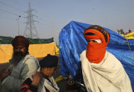 Nihangs or Sikh warriors stand outside their makeshift tents as they block a highway in protest against new farm laws at the Delhi-Uttar Pradesh state border, on the outskirts of New Delhi, India, Wednesday, Dec. 30, 2020. Protesting farmers fear the government will stop buying grain at minimum guaranteed prices and corporations will then push down prices. The government says the three laws approved by Parliament in September will enable farmers to market their produce and boost production through private investment. (AP Photo/Manish Swarup)