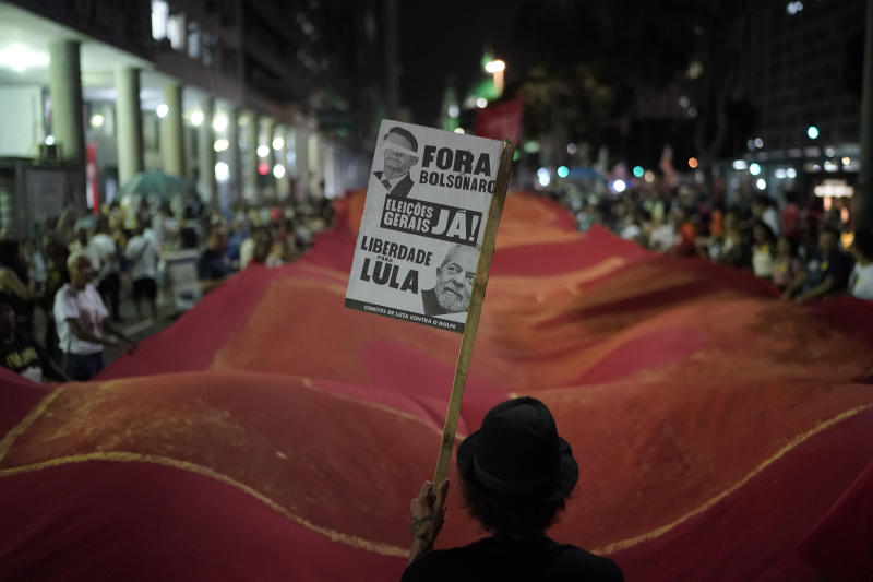 "A man carries a sign that reads in Portuguese ""Get out Bolsonaro,"" referring to the Brazil's President Jair Bolsonaro, as well as ""General elections now!"" and ""Freedom to Lula,"" during a protest against government-proposed pension reforms on the day of a nationwide strike in Rio de Janeiro, Brazil, Friday, June 14, 2019. The strike is the first since the arrival of far-right President Jair Bolsonaro on Jan. 1. (AP Photo/Leo Correa"