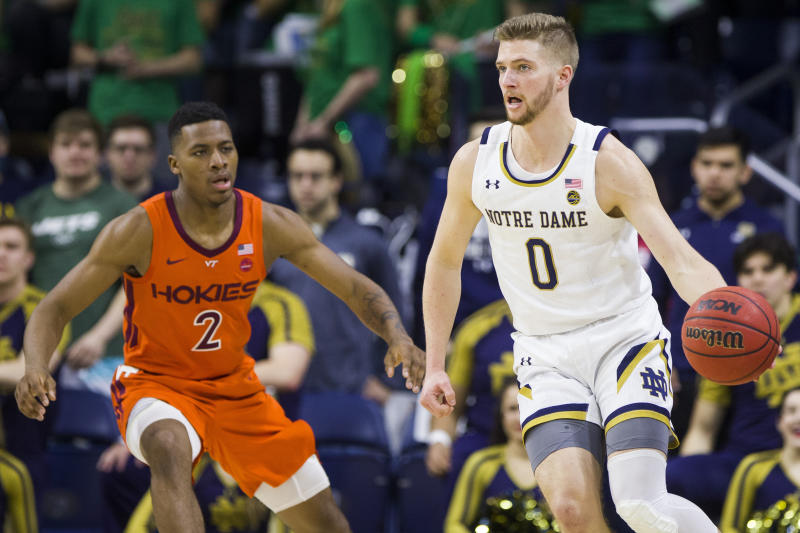 Notre Dame's Rex Pflueger (0) looks to pass around Virginia Tech's Landers Nolley II (2) during the first half of an NCAA college basketball game Saturday, March 7, 2020, in South Bend, Ind. (AP Photo/Robert Franklin)