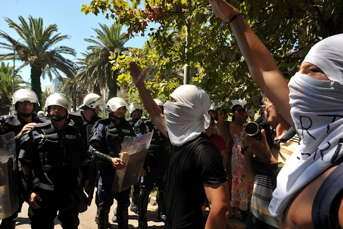 """Protesters shout slogans during the first ever pride event in the Montenegrin seaside resort of Budva, Wednesday, July 24, 2013. Dozens of extremists shouting """"Kill the gays"""" have attacked gay activists as they were gathering for the first ever pride event in staunchly conservative Montenegro. The assailants threw rocks, bottles and various other objects at some 20 gay activists and supporters and at special police securing the event in the coastal town of Budva on Wednesday. Police intervened to push the attackers away and the event continued as planned. (AP Photo/Risto Bozovic)"""