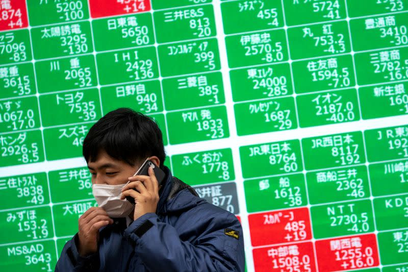 A man wearing a protective face mask talks on his mobile phone in front of a screen showing the Nikkei index in Tokyo