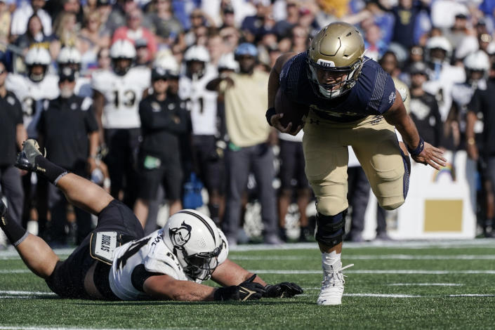 Navy quarterback Tai Lavatai, right, avoids a tackle by UCF defensive lineman Anthony Montalvo before scoring on a touchdown run during the first half of an NCAA college football game, Saturday, Oct. 2, 2021, in Annapolis, Md. (AP Photo/Julio Cortez)