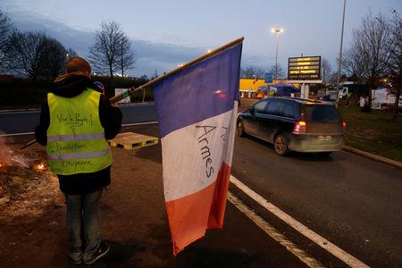 A protester wearing a yellow vest, the symbol of a French drivers' protest against higher diesel fuel prices, holds a flag at the approach to the A2 Paris-Brussels Motorway, in Fontaine-Notre-Dame, France, December 4, 2018.    REUTERS/Pascal Rossignol