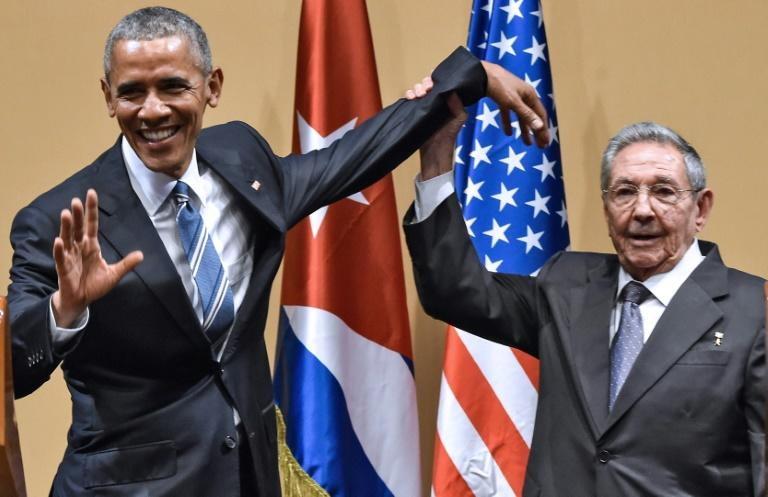 Cuban president Raul Castro raises US president Barack Obama's hand in Havana on March 21, 2016