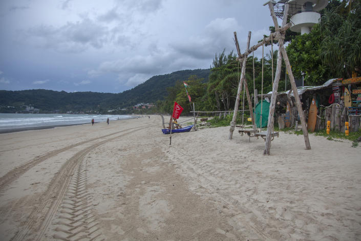 In this Wednesday, July 7, 2021, photo, tourists walk along a mostly empty Patong Beach on Phuket, southern Thailand. A week into an ambitious but risky plan to open the resort island of Phuket to fully-vaccinated visitors, signs were encouraging that the gambit to help breathe new life into the struggling tourism industry was working, even as coronavirus numbers in the rest of Thailand surged Thursday to new record highs. (AP Photo/Tiwa Suvarnabhanu)