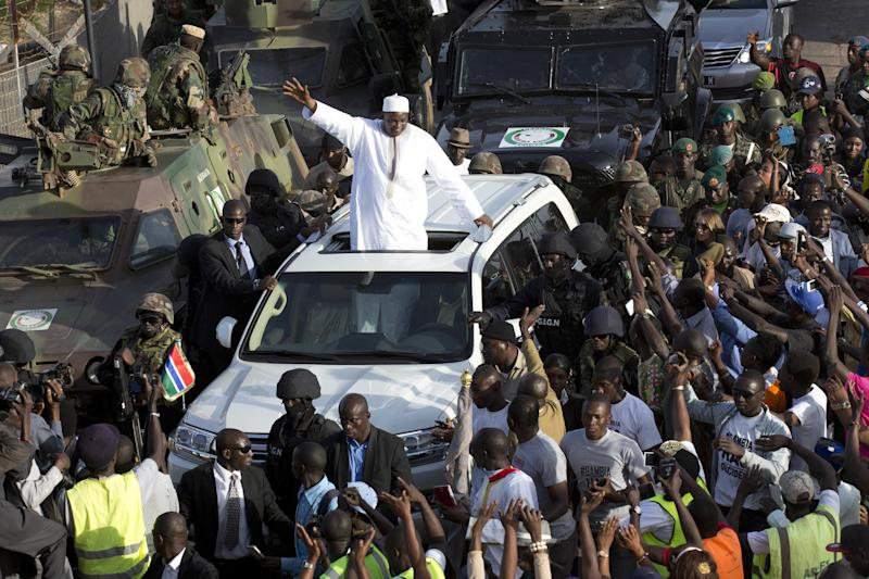 Gambian President Adama Barrow greets the crowds after arriving at Banjul airport in Gambia, Thursday Jan. 26, 2017, after flying in from Dakar, Senegal. Gambia's new president has finally arrived in the country, a week after taking the oath of office abroad amid a whirlwind political crisis. Here's a look at the tumble of events that led to Adama Barrow's return — and the exile of the country's longtime leader. (AP Photo/Jerome Delay)