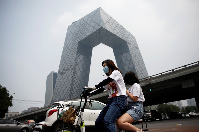 Woman wearing a face mask rides past the CCTV headquarters in Beijing