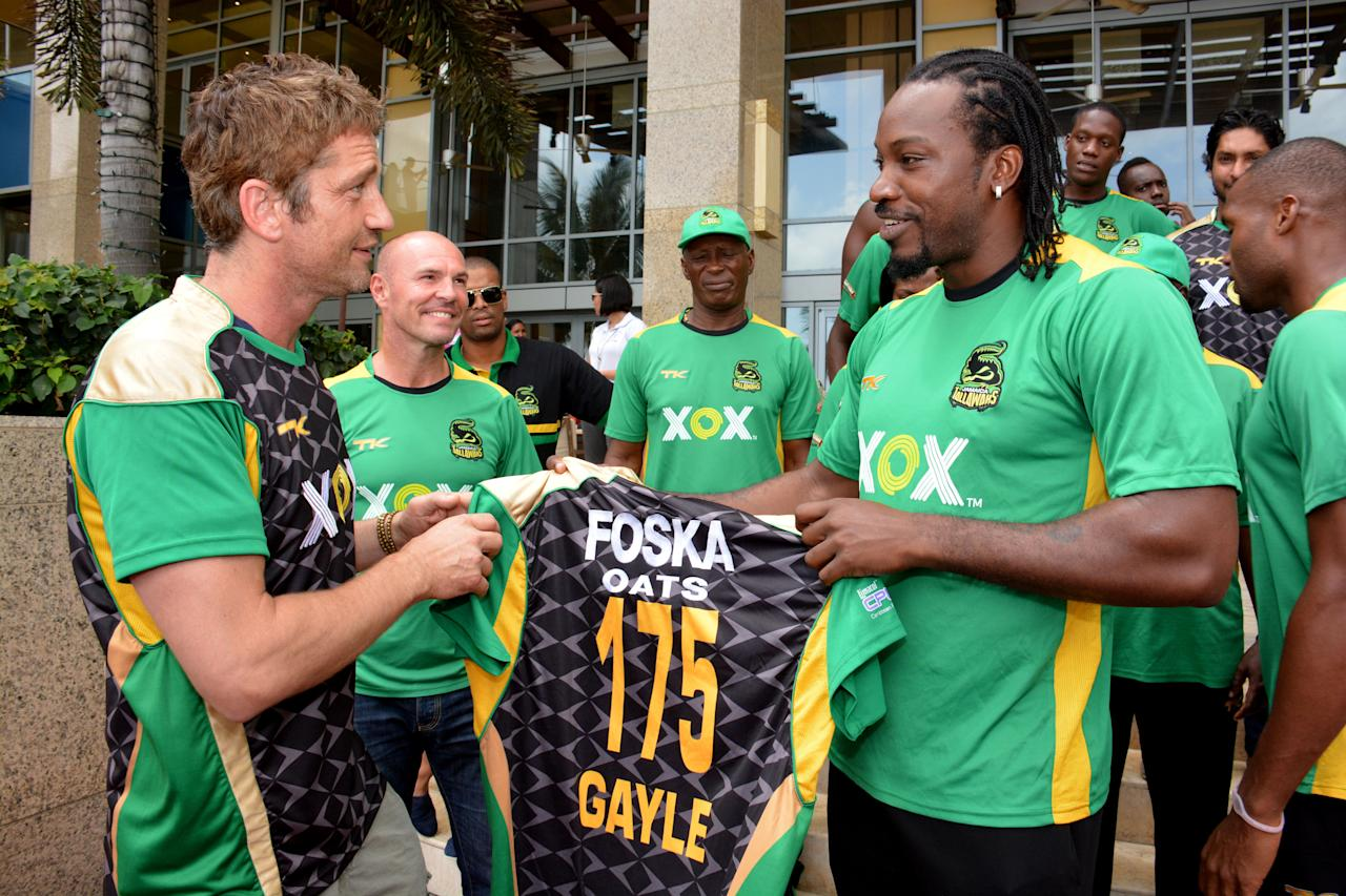 PORT OF SPAIN, TRINIDAD AND TOBAGO - AUGUST 23:  Actor Gerard Butler is presented with a Jamaica Tallawahs jersey by team captain, Chris Gayle August 23, 2013 in Port of Spain, Trinidad & Tobago. Butler has an equity interest in the Jamaica Tallawahs team, who is in the semi-final.  (Photo by Lloyd Pierre/Getty Images Latin America for CPL)