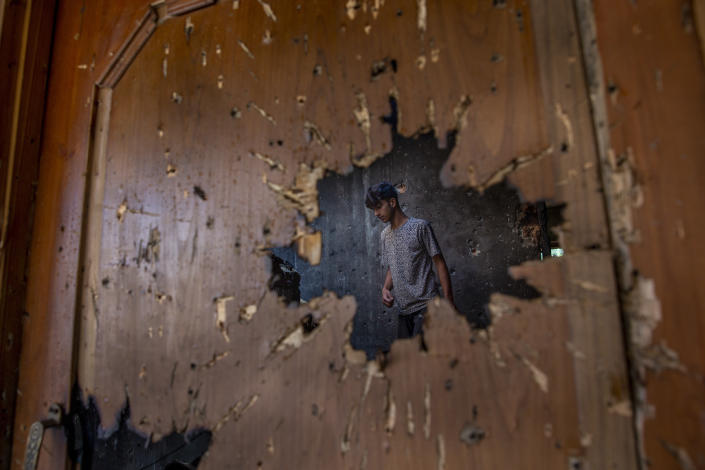 A Kashmiri inspecting a house where suspected rebels had taken refuge, is seen through a hole created by a mortar shell fired by government forces during a gunfight, in Srinagar, Indian-controlled Kashmir, Friday, July 16, 2021. Two suspected rebels were killed in a gunfight in in the disputed region's main city on Friday, officials said, as violence increased in recent weeks. (AP Photo/Dar Yasin)