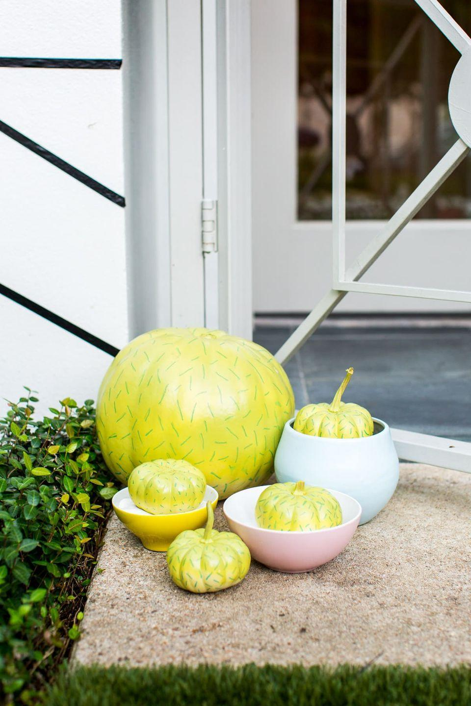 """<p>A dash of green paint turns ordinary pumpkins into extraordinary ones. Throw them into small, colorful pots to emphasize the resemblance. </p><p><strong>Get the tutorial at <a href=""""https://sugarandcloth.com/palm-springs-inspired-halloween-decor/"""" rel=""""nofollow noopener"""" target=""""_blank"""" data-ylk=""""slk:Sugar and Cloth"""" class=""""link rapid-noclick-resp"""">Sugar and Cloth</a>.</strong></p><p><strong><a class=""""link rapid-noclick-resp"""" href=""""https://go.redirectingat.com?id=74968X1596630&url=https%3A%2F%2Fwww.walmart.com%2Fip%2FApple-Barrel-Acrylic-Paint-Bright-Red-8-Oz%2F17301373%3FvariantFieldId%3Dactual_color&sref=https%3A%2F%2Fwww.thepioneerwoman.com%2Fholidays-celebrations%2Fg32894423%2Foutdoor-halloween-decorations%2F"""" rel=""""nofollow noopener"""" target=""""_blank"""" data-ylk=""""slk:SHOP GREEN PAINT"""">SHOP GREEN PAINT </a></strong></p>"""