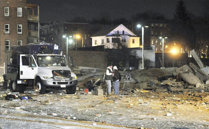 Gas company workers stand where a building once stood, which was leveled by an explosion in downtown Springfield, Mass. on Friday, Nov. 23, 2012. (AP Photo/Springfield Republican, Don Treeger) MANDATORY CREDIT