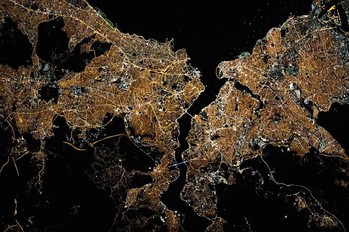 istanbul city grid lit up yellow gold at night with dark ocean waters and river splitting the city as seen from above