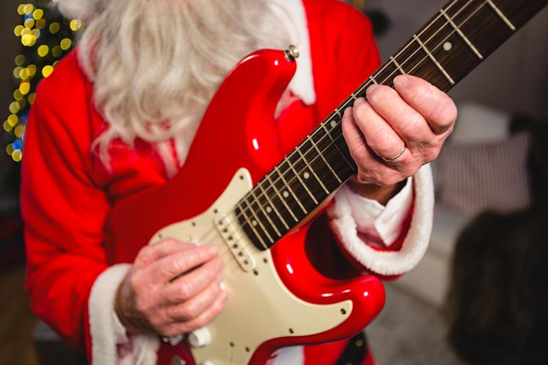 Mid-section of santa claus playing a guitar during christmas time at home